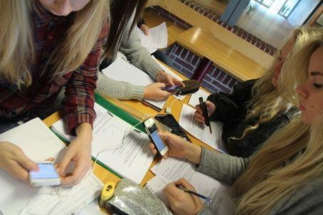 studerende med mobiler og opgaver
