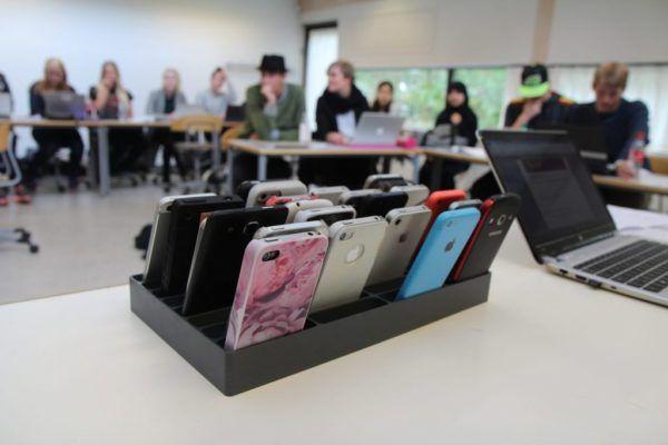 mobilramme fyldt med telefoner i klasselokale