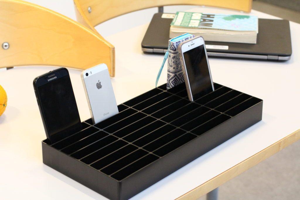 mobilrammen i sort på bord med fire telefoner